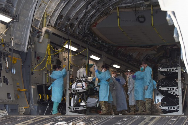 A COVID-19 patient who was being cared for at Madigan Army Medical Center, is loaded onto a C-17 Globemaster III by an aeromedical evacuation team from the 775th Expeditionary Aeromedical Evacuation flight from Travis Air Force Base, California, and other medical professionals from Madigan, at Joint Base Lewis-McChord, Washington, March 31, 2021. The patient was in severe respiratory distress and was hooked up to an extracorporeal membrane oxygenation (EMCO) system, which aids the body in breathing.