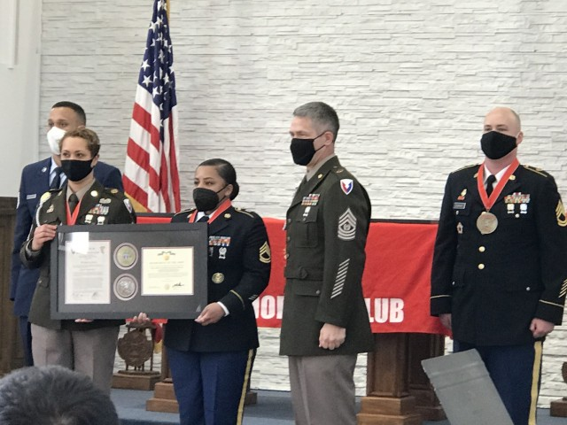 Air Force Tech Sgt. Francisco Lopez Rosario, left, and Sgt. 1st Class Gary Durham, right, stand at attention as Sgt. 1st Class Shannon Wyatt and USAG Wiesbaden Command Sgt. Maj. Christopher Truchon present Sgt. 1st Class Jasmine Brown with her framed certificate inducting her into the Sergeant Morales Club.