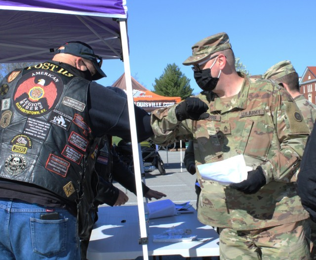 A member of the American Legion Riders elbow bumps a 1st Theater Sustainment Command Soldier at the safety stand down here, April 2, 2021. The riders are members of the Elizabethtown American Legion Post 113, and they sponsored the motorcycle safety training, which covered proper protective wear when operating a motorcycle for the Army and in the state of Kentucky.