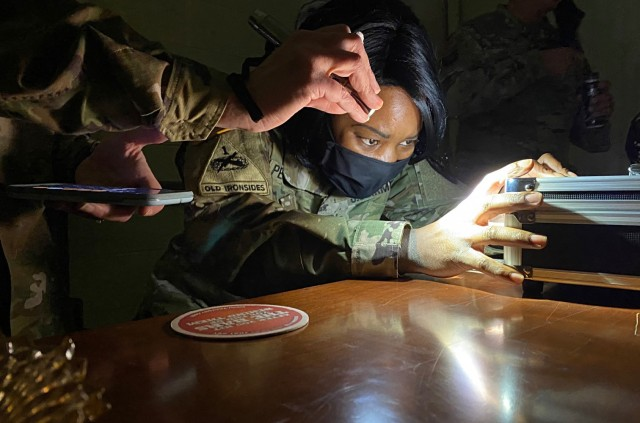 Sgt. 1st Class Saquawia V. Pennington, sexual assault response coordinator and creator of the RAPID Escape Room, 111th Military Intelligence Brigade, opens a lock box containing clues to a mystery in Fort Huachuca's RAPID Escape Room January 21, 2021. (U.S. Army photo by Meredith Mingledorff/Released)
