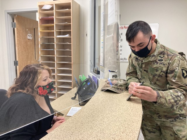 Sergeant Caleb Bobo, 101st Division Sustainment Brigade, 101st Airborne Division (Air Assault), talks to transportation specialist Charlsey Maples at the front desk of the Fort Campbell Transportation Office. He recently arrived at Fort Campbell after serving in South Korea and wanted to check on the shipping status of his goods.