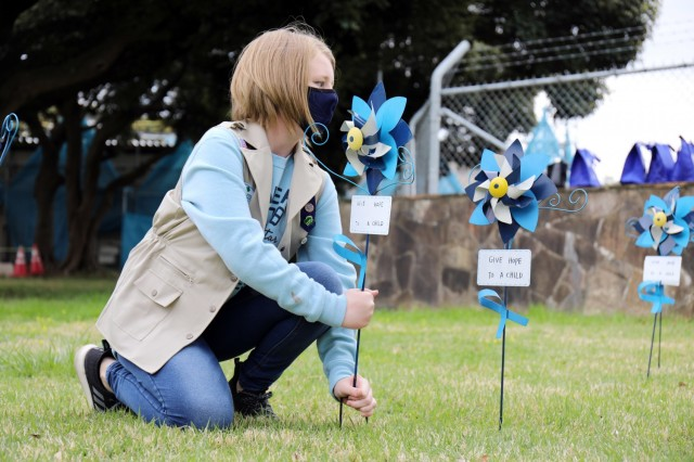 Kaitlyn Dodson, 12, a member of Girl Scout Troop 600, plants a pinwheel in honor of National Child Abuse Prevention Month at Camp Zama, Japan, April 6.