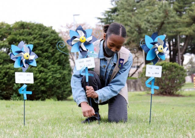 Naomi Thomas, 14, a member of Girl Scout Troop 600, plants a pinwheel in honor of National Child Abuse Prevention Month at Camp Zama, Japan, April 6.