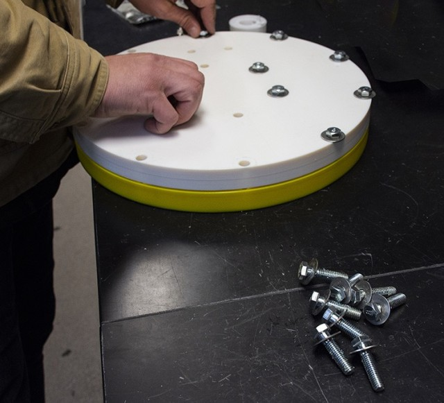"""The 3D printed test fixture is bolted together before placed in the SPiTFiRE (Swatch Permeation Test Fixture, Reengineered). The fixture holds 10 swatches of fabric that are exposed to chemical agent all at once, rather than individually in separate, sealed stainless steel """"cups"""" as previously done. Once contaminated to a certain (varied) point, the swatches are removed for measurement of off-gassing. The Air Force's Vapor Off-gassing Re-use Test (VORT) is conducted to determine if chemically contaminated aircrew clothing can be off-gassed long enough to the point where it may safely be reused. A variety of fabrics, taken from actual aircrew protective clothing, is used. If the pilot stage is successful, full testing will be funded by the Air Force.  Photo by Al Vogel, Dugway Public Affairs."""