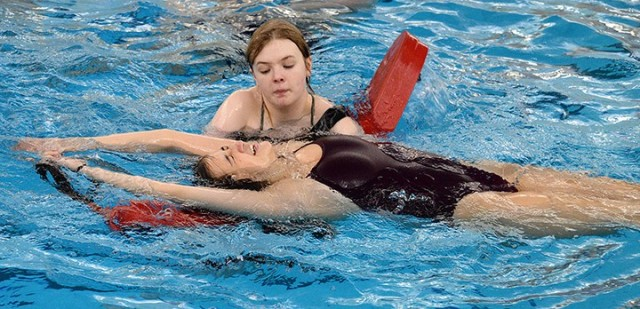 Kate Brooks uses momentum to pull Ashley Morgan onto a lifeguard rescue tube during lifeguard training April 3 at Harney Pool. Lifeguard training students took turns practicing rescues and portraying victims. Photo by Prudence Siebert/Fort Leavenworth Lamp