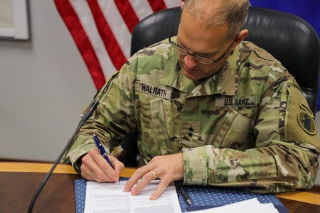 Maj. Gen. Daniel R. Walrath, Army South commanding general, signs the agreed-to-actions document between the U. S. and Salvadoran armies April 7, outlining future training commitments and professional exchanges between the two armies. (Photo by PFC Joshua Taeckens)