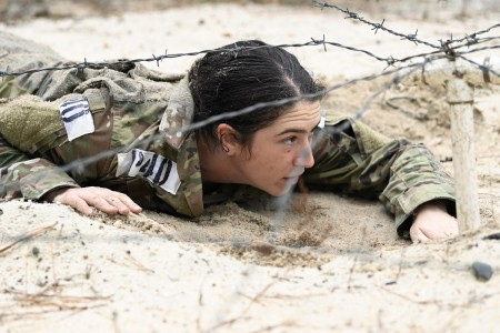 A soldier crawls under barbed wire during assessment and selection at Camp Mackall, N.C., March 1, 2021. Participants were evaluated on individual physical fitness and confidence, intelligence and psychological capability and ability to solve dilemma-based problems individually and as a team.