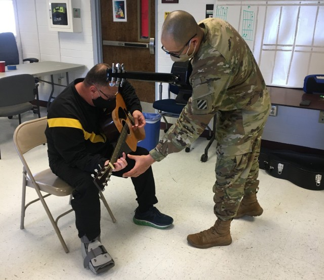 Spc. Jonathan Rodriquez teaches Lt. Col. Ken Sanders during a music lesson as part of the Adaptive Reconditioning Program. The 3rd Infantry Division Band provides volunteers to assist with an eight-week long Adaptive Reconditioning Program to teach guitar as part of recreational therapy. Photo by Sgt. Anthony Licata