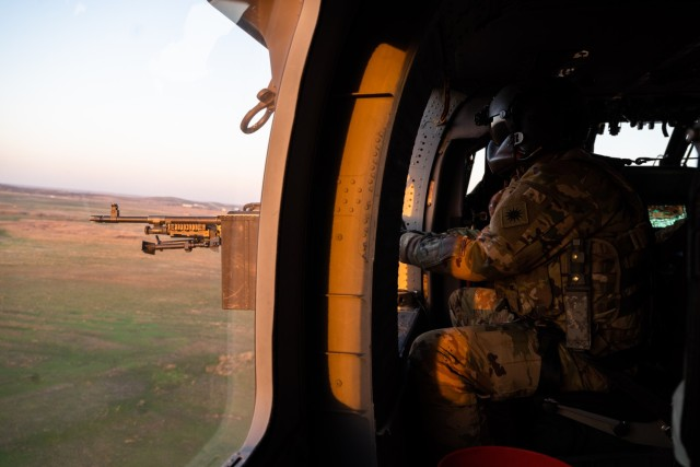 Spc. David Ngo, a UH-60 Black Hawk crew chief with C Company, 1st Assault Helicopter Battalion, 140th Aviation Regiment, Washington National Guard, engages targets during aerial gunnery qualifications at Fort Sill, Oklahoma, March 30, 2021.