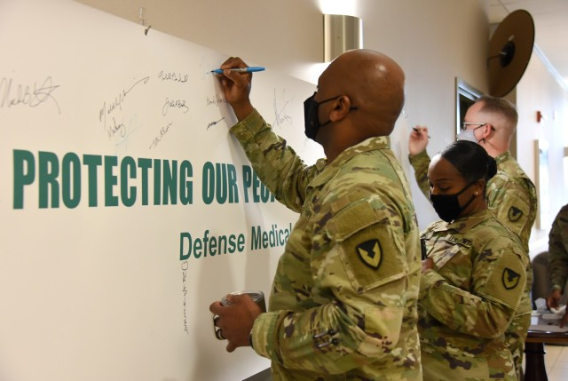 Col. Clayton Carr and others leaders at U.S. Army Medical Logistics Command sign a banner during a kickoff event April 2 to mark AMLC's month-long observance of Sexual Assault Awareness and Prevention Month at Fort Detrick, Maryland.