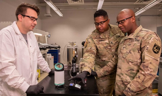 A. J. Roberts (left), shows a possible application from a nanogalvanic alloy discovery to Sgt. 1st Class Joiah Stewart (middle) Sgt. 1st Class Roderick Trotter (right).
