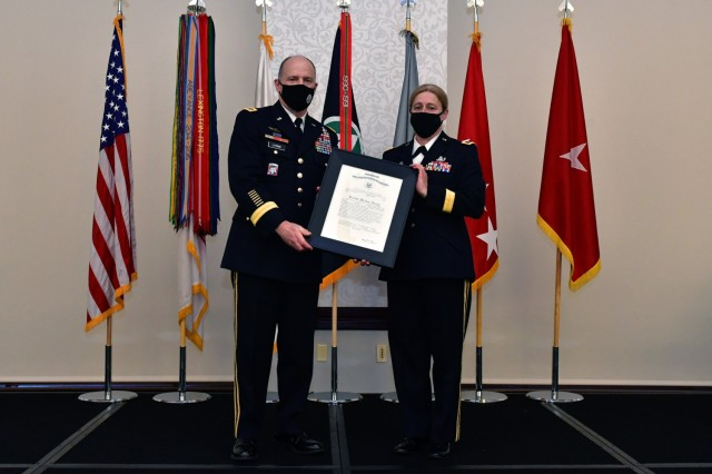 U.S. Army Gen. Stephen R. Lyons, commander U.S. Transportation Command, presents U.S. Army Brig. Gen. Heidi J. Hoyle with her promotion to major general order during a ceremony in her honor at the Scott Air Force Base, Ill. event center April 9, 2021.