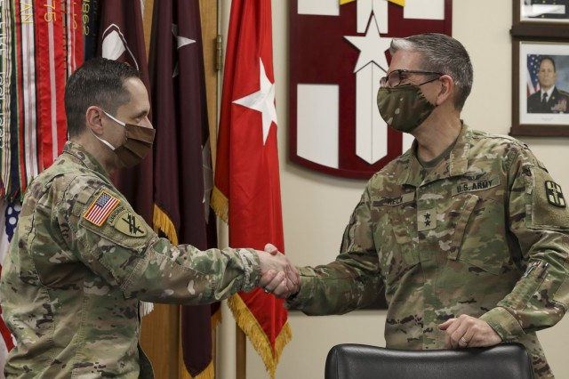 U.S. Army Maj. Gen. Joe Heck, 807th MC(DS) Commanding General, and Brig. Gen. Stephen Iacovelli, 94th TD Commanding General, shake hands following the signing of the Memorandum of Understanding instituting the Visiting Adjunct Instructor Program.  Iacovelli, presented Heck with a challenge coin for leading the way as the first medical command to support the program, April 8, 2021, Fort Douglas, Utah. (U.S. Army Reserve photo by Spc. Ronald D. Bell)