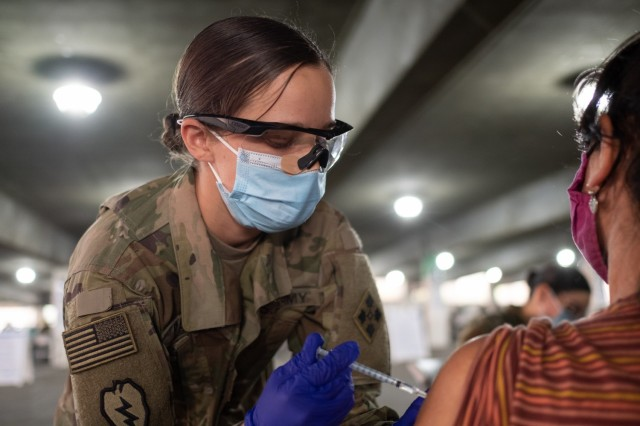 U.S. Army Staff Sgt. Kirsten Pavao of La Habra, Calif., a combat medic assigned to Headquarters and Headquarters Battery, 2nd Battalion, 12th Field Artillery Regiment, 1st Stryker Brigade Combat Team, 4th Infantry Division, administers the COVID vaccine at the California State University Los Angeles Community Vaccination Center, Feb. 26, 2021. Pavao vaccinated people at the CVC at Cal State LA. U.S. Northern Command, through U.S. Army North, remains committed to providing continued, flexible Department of Defense support to the Federal Emergency Management Agency as part of the whole-of-government response to COVID-19. (U.S. Army photo by Capt. Daniel Parker)