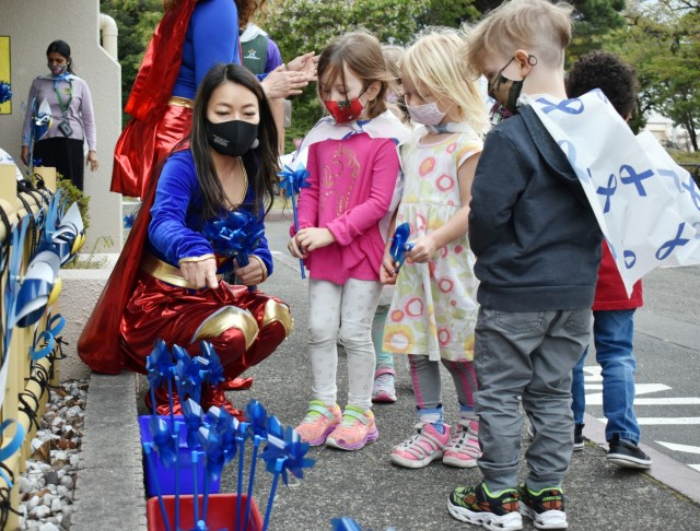 Sari Sugai, Exceptional Family Member Program manager for Army Community Service, helps, from left, Rose Withington, 4; Claire Herald, 3; and Torin Litton, 3, plant pinwheels at the Child Development Center at the Sagamihara Family Housing Area, Japan, April 9. Camp Zama Family and Morale, Welfare and Recreation officials held a superhero parade and the pinwheel planting in honor of the Month of the Military and National Child Abuse Prevention Month.