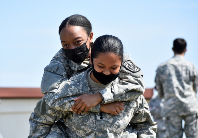 Cadet Capt. Raelyn Flores, right, practices a medical rescue carry with Cadet Staff Sgt. Theori Lindsay during the Zama Middle High School Junior Reserve Officers' Training Corps Cadet Leadership Challenge at Kastner Army Airfield, April 8.
