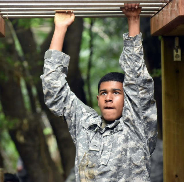 Cadet Pvt. Stanley Green completes the monkey bars portion of the obstacle course during the Zama Middle High School Junior Reserve Officers' Training Corps Cadet Leadership Challenge at Camp Zama, Japan, April 6.