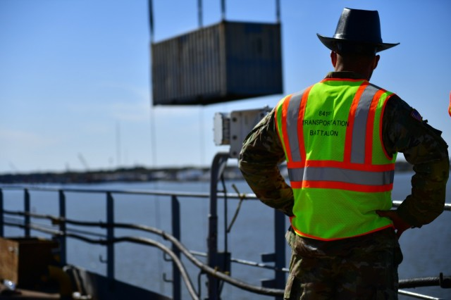 Chief Warrant Officer 2 Jordan Milo, a mobility warrant officer from the 841st Transportation Battalion, Charleston, South Carolina and the DEFENDER-Europe 21 Port of Portsmouth Operations Officer in Charge oversees Joint Logistics Over-The-Shore container lift operations at the Port of Portsmouth, Va. April 3, 2021.