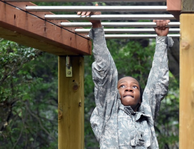 Cadet Maj. Queen Thomas completes the monkey bars portion of the obstacle course during the Zama Middle High School Junior Reserve Officers' Training Corps Cadet Leadership Challenge at Camp Zama, Japan, April 6.