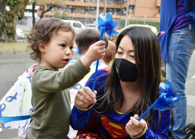 Sari Sugai, Exceptional Family Member Program manager for Army Community Service, helps Ezra Stallings, 2, plant a pinwheel at the Child Development Center at the Sagamihara Family Housing Area, Japan, April 9. Camp Zama Family and Morale, Welfare and Recreation officials held a superhero parade and the pinwheel planting in honor of the Month of the Military and National Child Abuse Prevention Month.