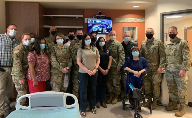 Members of the CRDAMC tele-critical care launch team stand in front of one of twelve newly installed video monitors that will serve as a technology-driven patient care platform linking providers and their patients with board-certified intensivists. (Courtesy photo)