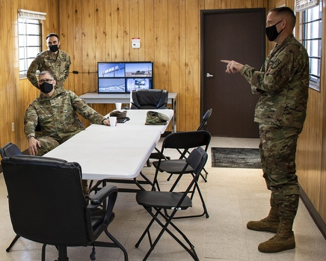 Major figures in the tests and upgrading of the Missile Warning System (MWS) visited Dugway Proving Ground recently. Left, sitting: Col. Kevin Chaney, Project Manager, AircraftSurvivability Equipment. Left, standing: Maj. Nathan Klein, Assistant Program Manager for MWS. Right: Col. Marcus A. Gengler, director of Aviation Enablers – Requirements Determination Directorate. Here, they are discussing a presentation they just watched about the MWS test.