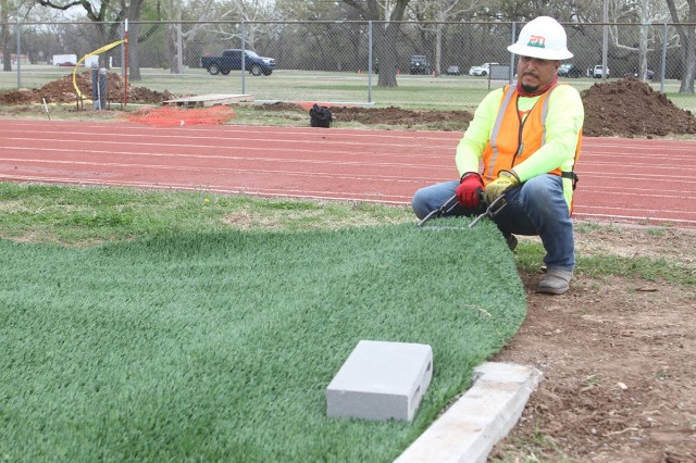 Carlos Nambo of Pro Turf Incorporated of Haslet, Texas, pulls slack out of a section of artificial turf April 9, 2021 on the infield of the Prichard Field track here. The synthetic multipurpose field will primarily be used for Army Combat Fitness Test purposes.