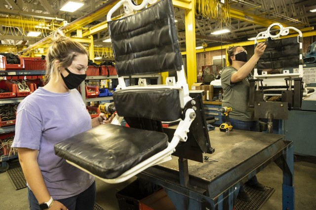 ABOVE: Robin Hurst (left) and Evelyn Wilke, student trainee laborers in the Pathways Technical College program, reassemble troop seats for a Stryker vehicle.