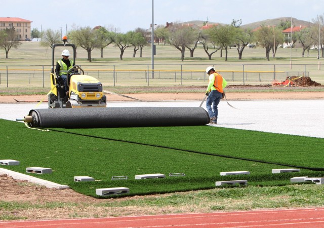 Adam Garley of Pro Turf Incorporated of Haslet, Texas, rolls out a 15-foot by 100-foot section of artificial turf April 9, 2021, at Prichard Field. Once all turf was placed, Pro Turf workers glued the sections together then nailed the perimeter down to the fine gravel base underneath.