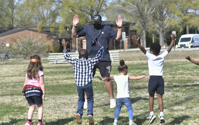 Jordan M. Fields, Child and Youth Services functional fitness instructor, leads a Child Development Center exercise session April 7 at the CYS athletics field. Fields has developed numerous programs for the children that include drills, exercises and games (photo by T. Anthony Bell).