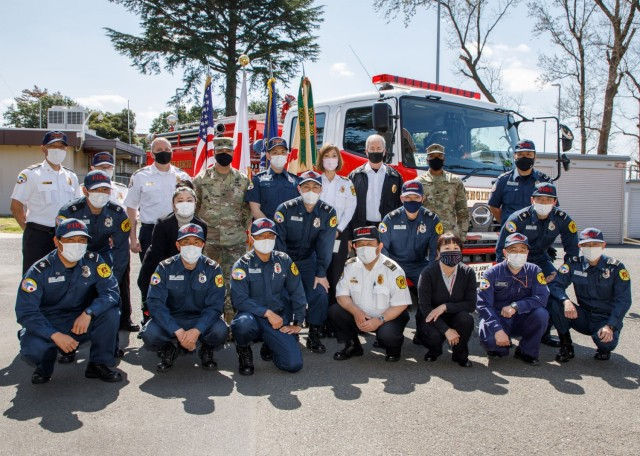 Col. Thomas Matelski, rear left in the Army uniform, commander of U.S. Army Garrison Japan; and USAG Japan Command Sgt. Maj. Justin Turner, rear right in the Army uniform, recognize the garrison's fire department at Camp Zama, Japan, March 23, for winning the Department of Defense Fire and Emergency Services Annual Firefighter Awards' best in the Pacific award. Regional Fire Chief Frank Wombwell stands to the right of Turner, and Regional Deputy Fire Chief Richard Juday stands to the right of Matelski.