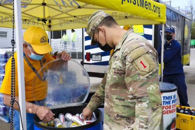 James Crabtree, left, a volunteer with the Texas Baptist Ministry, offers a drink to U.S. Army Spc. Kevin Kalnai, a combat medic assigned to 2nd Battalion 70th Armor Regiment, 2nd Armored Brigade Combat Team, 1st Infantry Division, at the Fair Park Community Vaccination Center (CVC) in Dallas, April 7, 2021. Crabtree, a former U.S. Air Force Airman, has been a disaster relief volunteer since 2017. U.S. Northern Command, through U.S. Army North, remains committed to providing continued, flexible Department of Defense support to the Federal Emergency Management Agency as part of the whole-of-government response to COVID-19. (U.S. Army photo by Spc. Alvin Conley, 19th Public Affairs Detachment)