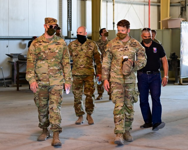 U.S. Army Capt. Stephen Long, executive officer, 401st Army Field Support Battalion-Qatar (left), guides Col. Michael F. LaBrecque, commander, 401st Army Field Support Brigade, and AFSBn-Qatar leadership through an empty warehouse during a 401st AFSB command circulation at Camp As Sayliyah, Qatar, Apr. 6.  The command team visit was conducted to reinforce moral and monitor the progress of AFSBn-Qatar's deactivation operations. (Photo by Capt. Luis Alani, 401st AFSB Public Affairs)