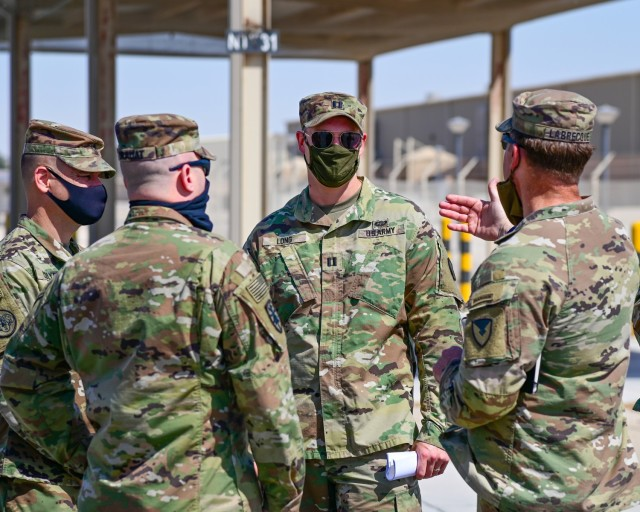 U.S. Army Capt. Stephen Long, executive officer, 401st Army Field Support Battalion-Qatar (center), listens to Col. Michael F. LaBrecque, commander, 401st Army Field Support Brigade (right) as he discusses the timeline and expectancies for complete AFSBn-Qatar deactivation, at Camp As Sayliyah, Qatar, Apr. 6.  (Photo by Capt. Luis Alani, 401st AFSB Public Affairs)