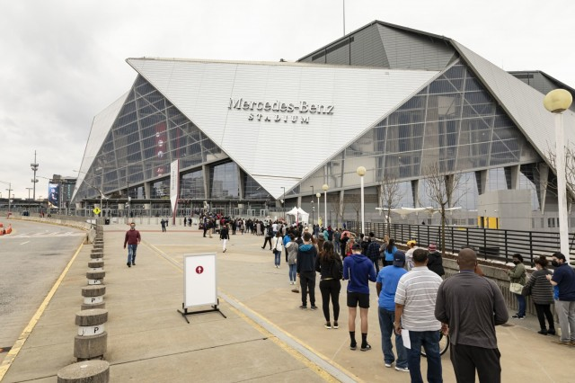 Community members wait outside to enter the Mercedes-Benz Stadium, site of the Atlanta Community Vaccination Center, on opening day March 24, 2021. U.S. Northern Command, through U.S. Army North, remains committed to providing continued, flexible Department of Defense Support to the Federal Emergency Management Agency as part of the whole-of-government response to COVID-19. (U.S. Army Photo by Spc. Robert P Wormley III, 50th Public Affairs Detachment)