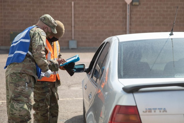 U.S. Army Sgt. Ethan McKinnon, left, and Pfc. Tuan Tran, right, combat medics assigned to 2nd Stryker Brigade Combat Team, 4th Infantry Division, screen a Pueblo community member prior to receiving a vaccination in Pueblo, Colorado, April 13, 2021. The Soldiers deployed from Fort Carson, Colorado to administer vaccinations to members of the Pueblo community to support the federal vaccination effort. U.S. Northern Command, through U.S. Army North, remains committed to providing continued, flexible Department of Defense support to the Federal Emergency Management Agency as part of the whole-of-government response to COVID-19. (U.S. Army photo by Spc. Jacob Moir)