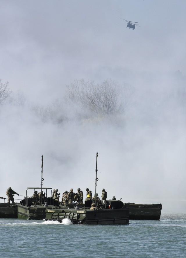 A CH-47 Chinook helicopter circles overhead as bridge crewmember trainees from Company A, 35th Engineer Battalion, prepare to build float bridges on the lake at TA 250 while smoke obscures their view during the FTX.