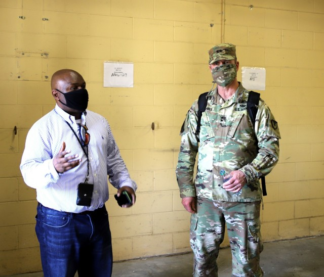 Fort Stewart, Ga - Kevin Lewis, chief, Installation Supply Division, 406th Army Field Support Battalion (left), shows Maj. Gen. Daniel Mitchell, commanding general, U.S. Army Sustainment Command, one of the rooms that will be used to temporarily store non-rolling stock as it gets processed through the Modernization Displacement and Repair Site at Fort Stewart, Georgia, April 13, 2021.  (Photo by Sgt. 1st Class Corey Baltos, U.S. Army Sustainment Command)