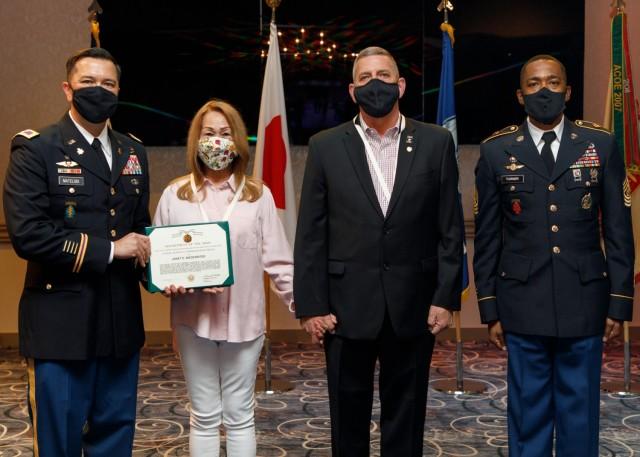 U.S. Army Garrison Japan commander Col. Thomas Matelski (left) and Command Sgt. Major Justin Turner (right) present Janet Niederriter with the Public Service Commendation Medal during J. Steve Niederriter's retirement ceremony April 16, 2021, at Camp Zama, Japan.