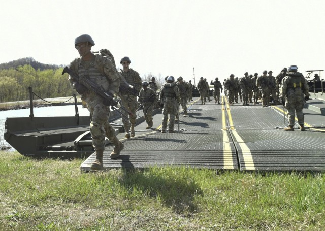 Combat engineer trainees from Company A, 35th Engineer Battalion, depart a float bridge after crossing the lake at Training Area 250 as part of their culminating field training exercise.