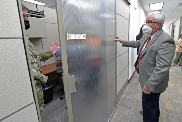 Maj. Ryan McMahon, Professor of Surgery and Director of Basic Life Support, demonstrates the sliding door of his new office partition to Mr. J.M. Harmon III, Deputy to the MEDCoE Commanding General.