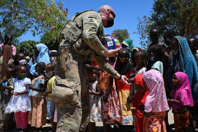 A soldier hands out candy to children in Lamu, Kenya, March 20, 2021. Soldiers collected donations from loved ones in the U.S. to support the humanitarian effort in the region.