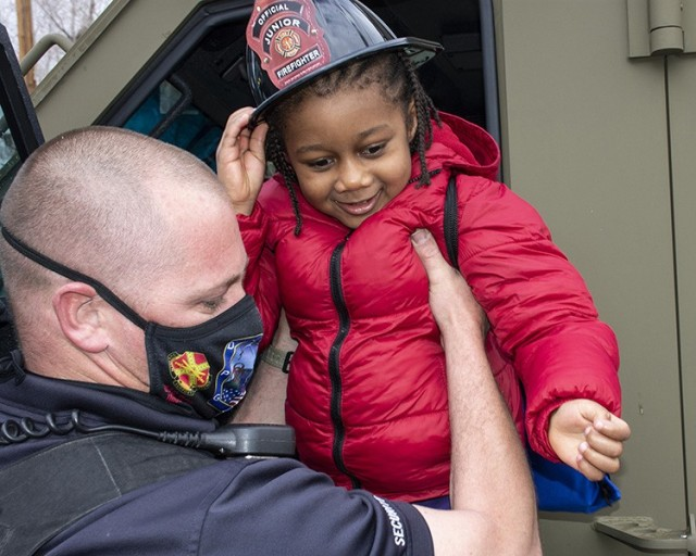 With his new Official Junior Firefighter hat held firmly, this youngster gets help coming out of a Bearcat escalated response vehicle from a Dugway Proving Ground police officer. The boy and his sister, their birthdays close, received a visit to their home's curb by Dugway emergency vehicles, Emergency personnel began making the siren-filled visit and vehicle tour for youngsters, after COVID-19 eliminated birthday parties. Parents call the police dispatcher to schedule a visit. Photo by Al Vogel, Dugway Public Affairs