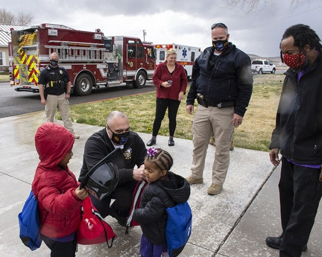 Dugway Proving Ground Assistant Fire Chief Patrick Carnahan helps a girl with her jacket during a curbside visit of Emergency Medical Services vehicles and personnel to her home. Her brother, whose birthday is also near to hers, looks on. The siren-filled visit was created for Dugway kids, to reduce the disappointment of not being able to have a birthday party due to coronavirus restrictions. Dugway residents call the dispatch center to schedule a visit. Photo by Al Vogel, Dugway Public Affairs