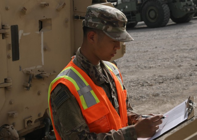 Army Reserve Spc. Feiyu He, a yard specialist deployed to Camp Arifjan, Kuwait, with the Lancaster, Pennsylvania-based 1185th Deployment and Distribution Support Battalion, reviews paperwork March 26, 2021 for rolling stock at Kuwait's Shuaiba Port. Chinese-born He is applying for U.S. citizenship with the support of the 1st Theater Sustainment Command's operational command post at the camp. (U.S. Army photo by Staff Sgt. Neil W. McCabe)