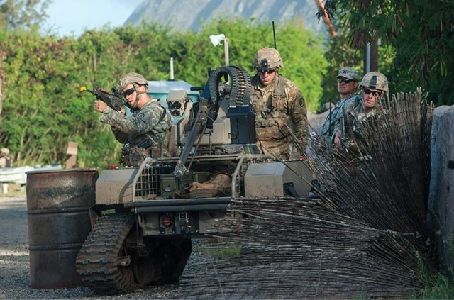 25th Infantry Division Soldiers move toward a simulated opposing force with a Multipurpose Unmanned Tactical Transport during training in Hawaii.
