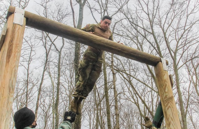 U.S. Military Academy Black Team leader Class of 2021 Cadet John Sweeney leaps to the higher log to get across the obstacle known as the 'dirty name' during the 52nd Sandhurst Military skills competition on April 17. Cadets mount the low log and jump onto the middle log. Cadets pull themselves onto the middle log and jump onto the high log. Then they grasp over the top of the log with both arms keeping their belly area in contact with it. They swing their legs over the log, then lower themselves to the ground.