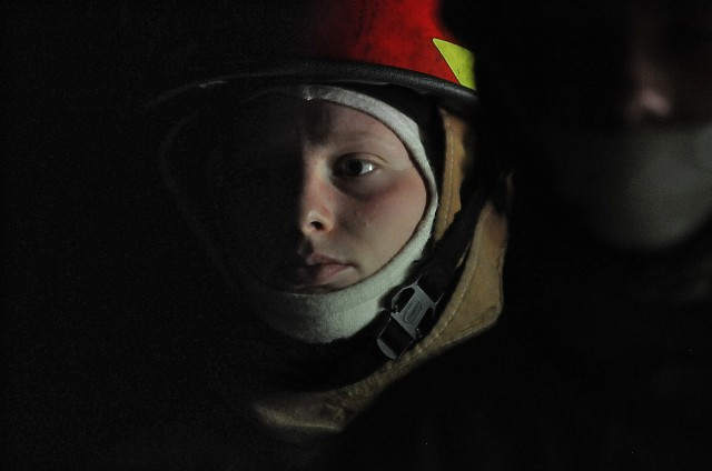 Pvt. Sidney Little, an 88K Watercraft Operator Course student, listens to the brief with other students in the darkness of the fire trainer April 16 at Joint Base Langley-Eustis. Little and her classmates would later don equipment to fight flames in smoke-filled, dark spaces with temperatures over 300-degrees.
