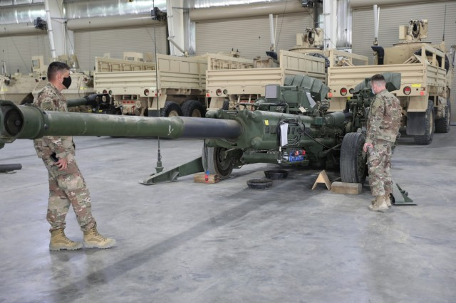 Soldiers from the 1st Theater Sustainment Command, Operational Command Post observe equipment which has been staged as part of the 401st Army Field Support Battalion-Kuwait's and the Army's Prepositioned Stock program at Camp Arifjan, Kuwait on April 3, 2021. (U.S. Army photo by Capt. Elizabeth Rogers)