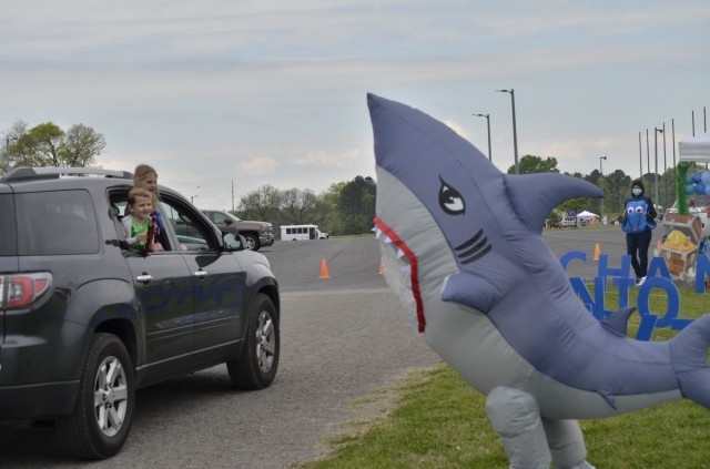 Fort Campbell children smile and wave at a friendly shark from an aquatic-themed Parent Central Services display April 17 during Kidsfest: Magical Drive-thru, hosted by Morale, Welfare and Recreation at the division parade field. Families traveled the parade route by car, passing colorful displays and costumed characters as employees from across the installation cheered the children for their strength and resilience.